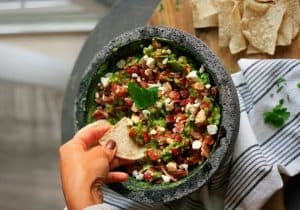 Guacamole with goat cheese, bacon, and maple-chipotle drizzle